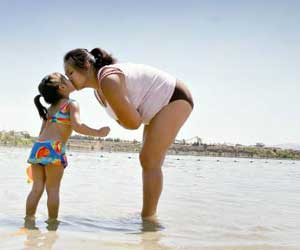 A sunny, sweet kiss between mom and child